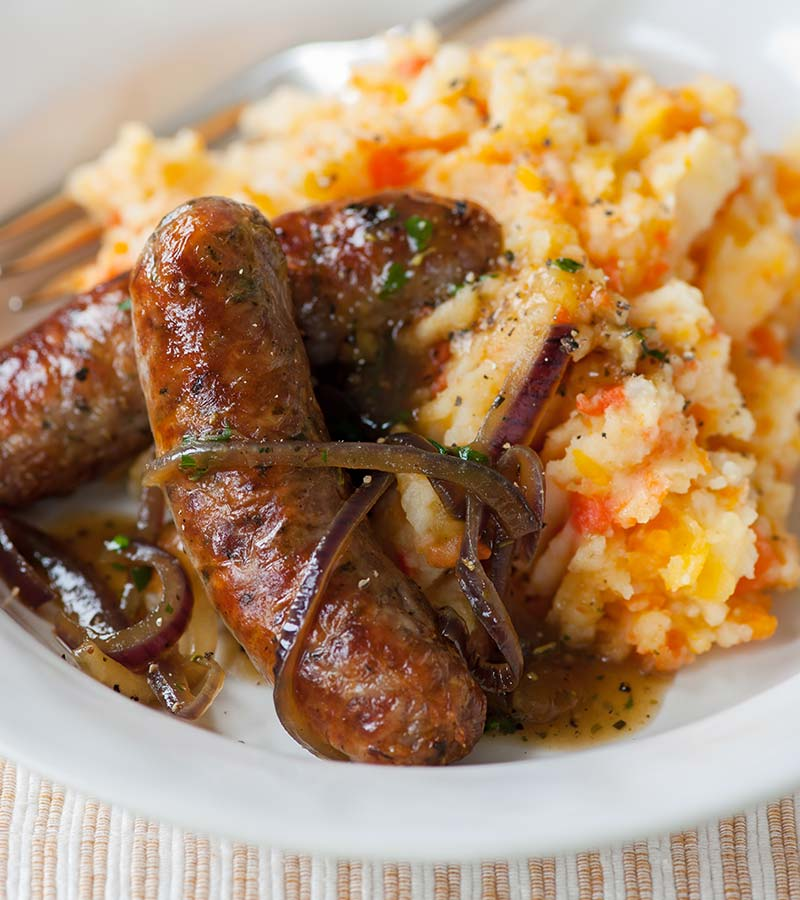 Sizzling sausages and mixed mash with red onion gravy